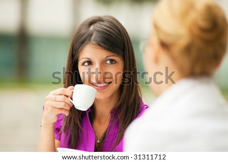two business women drinking coffee outdoors - stock photo