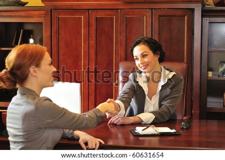 two business women greeting each other in an office meeting - stock photo