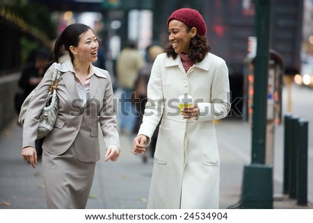 Two business women having a conversation while walking in the big city. - stock photo