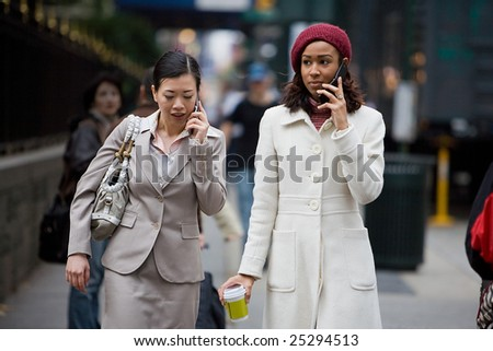 Two business women having conversations on their cell phones while walking in the big city. - stock photo