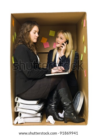 Two Business women in a very small Cardboard office isolated on white background