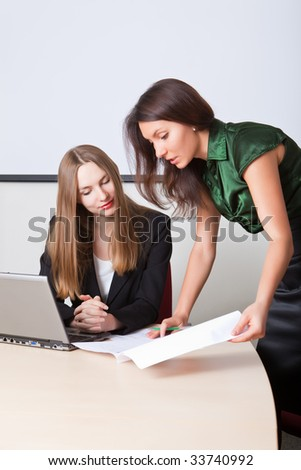 Two business women read documents
