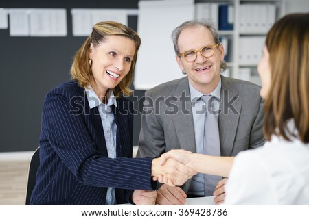 Two business women shaking hands at the end of a meeting between an investment broker and a middle-aged couple planning their retirement