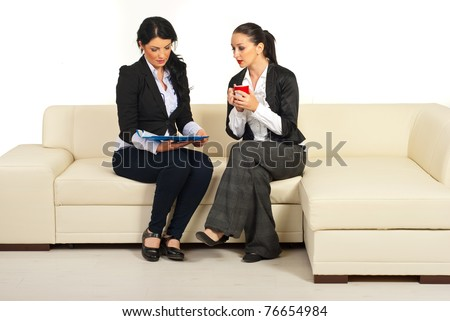 Two business women sitting on couch reading folders and having conversation
