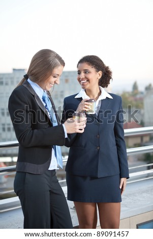 two business women talking and drinking coffee