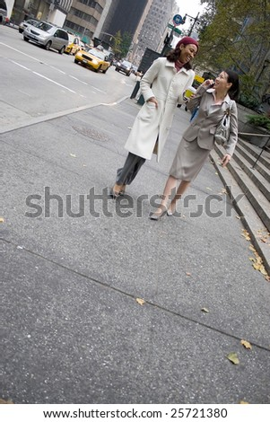 Two business women walking in the big city with plenty of copy space. One woman is on her cell phone. - stock photo