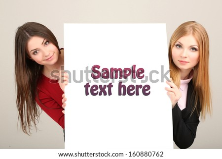 Two business women with blank form on grey background - stock photo
