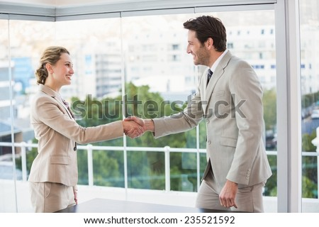 Two business workers shake hands in the office - stock photo
