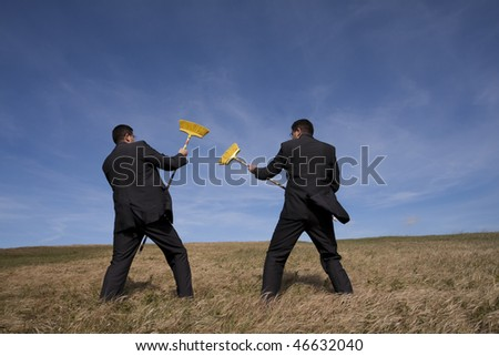 two businessman at the field fighting with brooms - stock photo