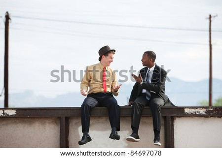 Two businessman chat while sitting on a wall