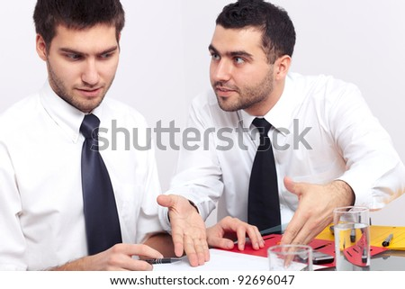 Two businessman have an argument over some paperwork. - stock photo