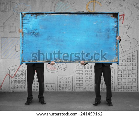two businessman hold old blue blank wooden billboard stand on concrete floor with doodles wall background - stock photo