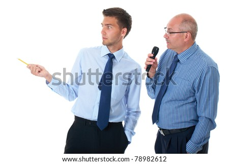 two businessman in blue shirt during seminar presentation, one point to left with yellow pencil, the other speaks to microphone, isolated on white - stock photo