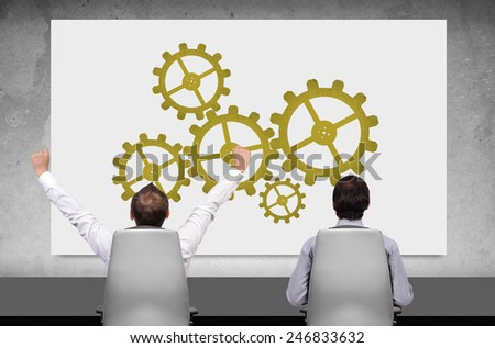 two businessman looking on placard with gears - stock photo