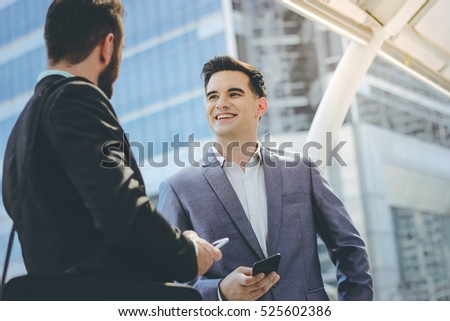 Two businessman meeting and holding smartphone at sidewalk of the modern building