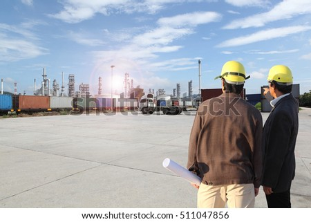 two businessman or engineering man working at Chemical Industry, Storage Tank And Tanker Truck In Industrial Plant