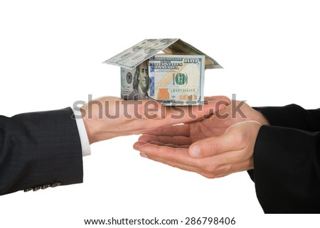 Two Businessman's Hand Holding House Made Of American Dollar Over White Background - stock photo