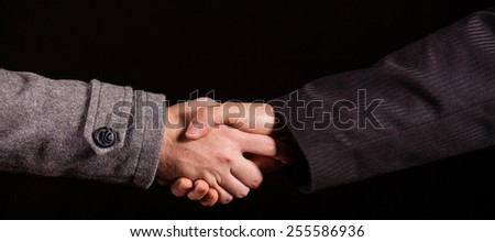 Two businessman shaking hands over black - stock photo