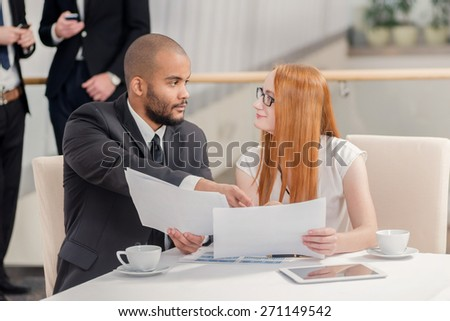 Two businessman sitting at the table and discussing business and keep documents in their hands while their colleagues standing in the background and shake hands - stock photo