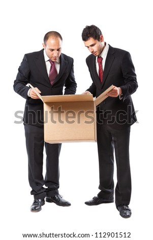 Two Businessman standing on a white background and looking inside a box - stock photo