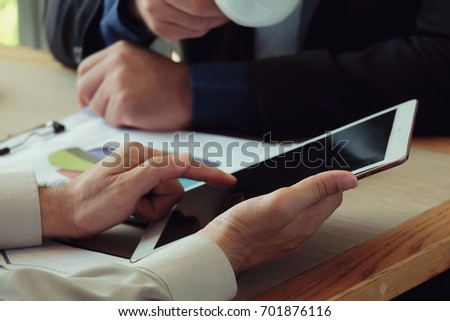 Two businessman working on tablet, partner discuss plan or idea at meeting
