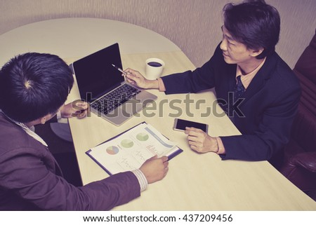 Two businessmen are now focusing on the details on the documents in front of them. - stock photo