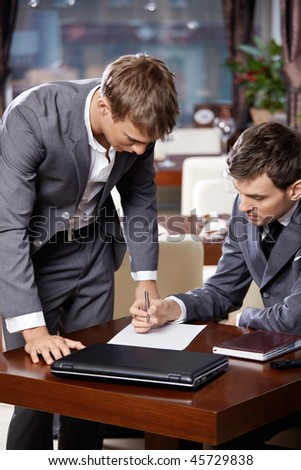 Two businessmen at restaurant consider the document - stock photo