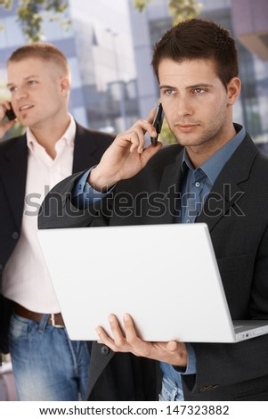 Two businessmen busy making phone call, using mobile, holding laptop computer, standing outside of office. - stock photo
