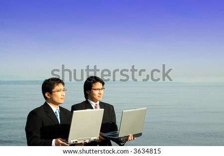 Two businessmen carrying their laptops on the beach - stock photo