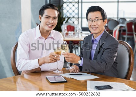 Two Businessmen Celebrating Success in Restaurant