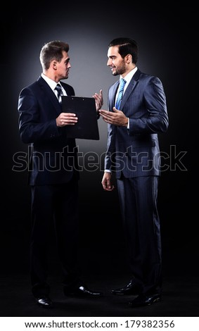 Two businessmen discussing, isolated over black background - stock photo