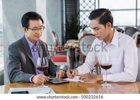 Two Businessmen Discussing Project in Restaurant