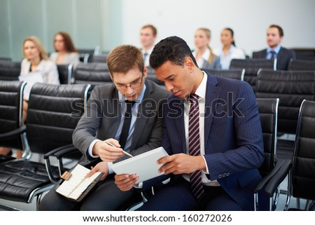 Two businessmen discussing something in touchpad at seminar on background of their colleagues - stock photo
