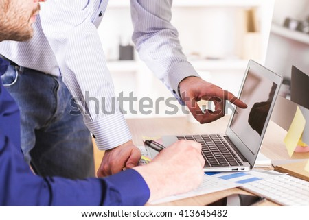 Two businessmen discussing something, pointing at laptop screen placed on business chart - stock photo