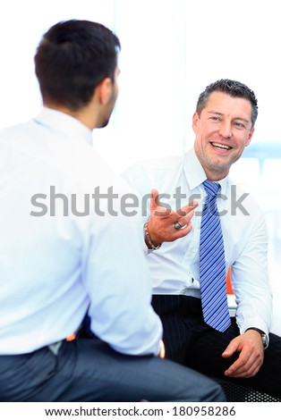 Two businessmen discussing tasks sitting at office table - stock photo