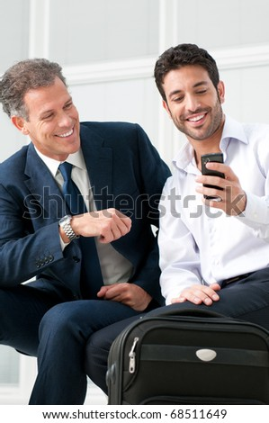 Two businessmen discussing together on a news on a smart phone during a business travel - stock photo