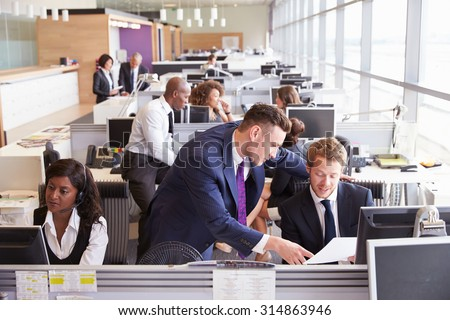 Two businessmen discussing work in a busy, open plan office - stock photo
