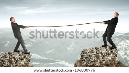 Two businessmen doing tug of war - stock photo