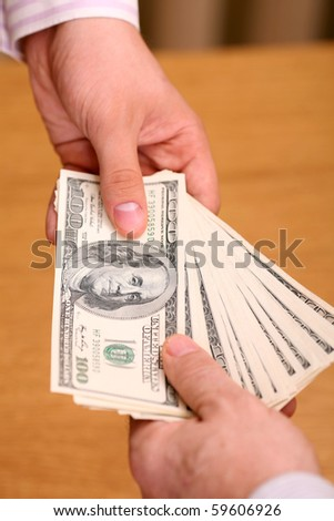 Two businessmen giving and taking dollars over wooden background - stock photo