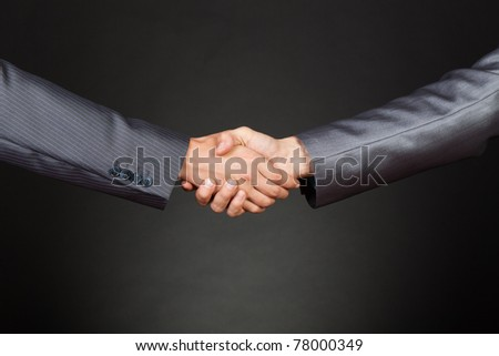 Two businessmen hands in elegant suits handshake over gray dark background. Communication, greeting, agree, congratulation meeting concept. - stock photo