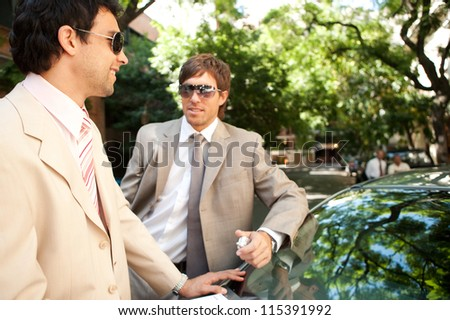Two businessmen having a conversation while leaning on a car in a tree lined street in the city, smiling. - stock photo