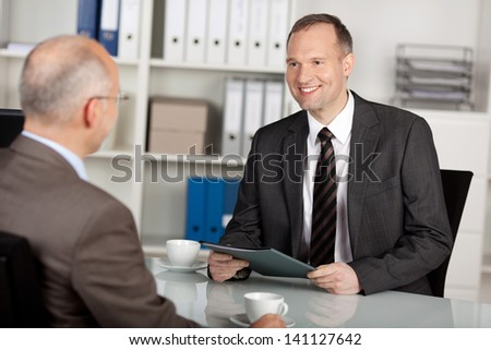 Two businessmen having conversation inside the office - stock photo