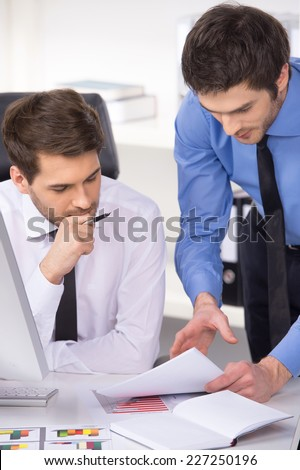 two businessmen having discussion in office. Two businessmen looking at charts and graphs on table - stock photo