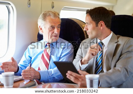 Two Businessmen Having Meeting On Train - stock photo