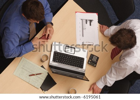 Two businessmen in a discussion, looking at laptop, paperwork; shot from above. - stock photo