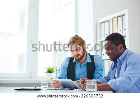 Two businessmen in casual discussing data in touchpad - stock photo