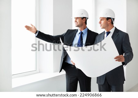 Two businessmen in suits indoors - stock photo