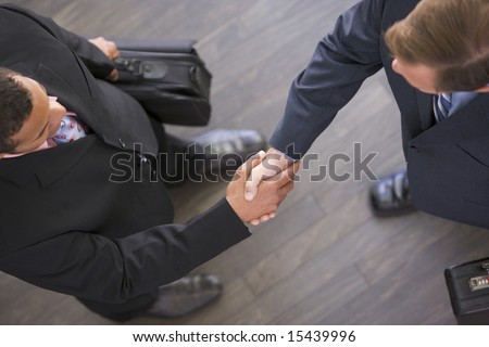 Two businessmen indoors shaking hands - stock photo