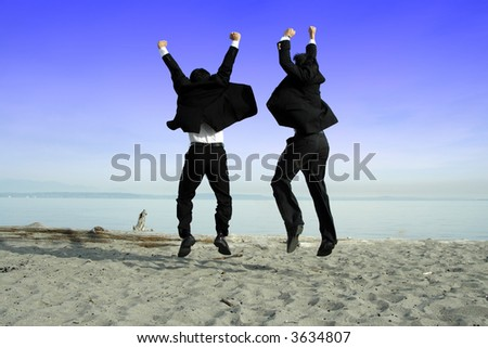 Two businessmen jumping and celebrating on the beach - stock photo