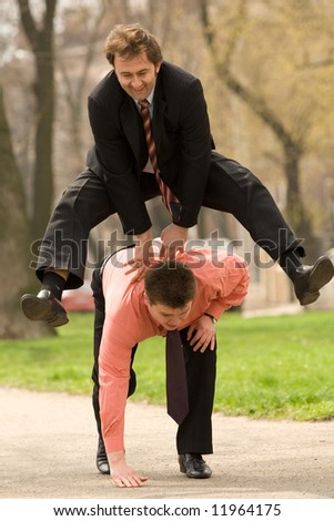 Two businessmen  jumping, playing leapfrog - stock photo